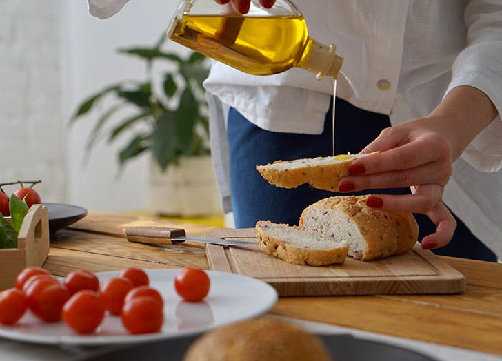 Woman pouring anti inflammatory olive oil on bread