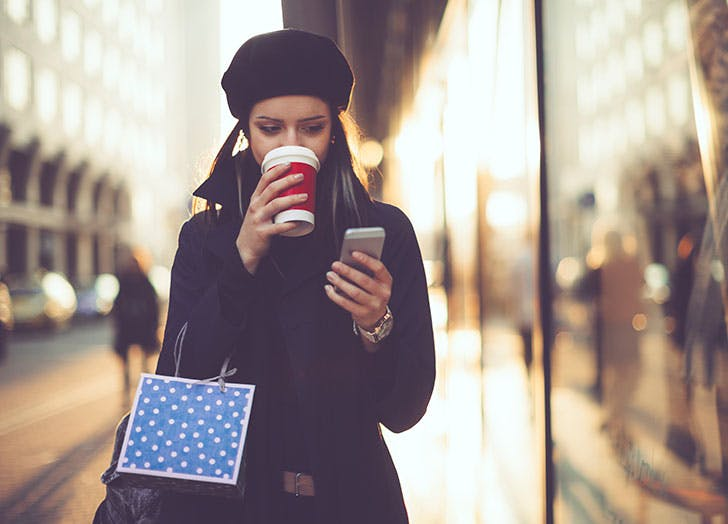 Woman shopping and drinking Starbucks coffee