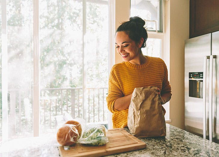 Woman unpacking healthy groceries in kitchen