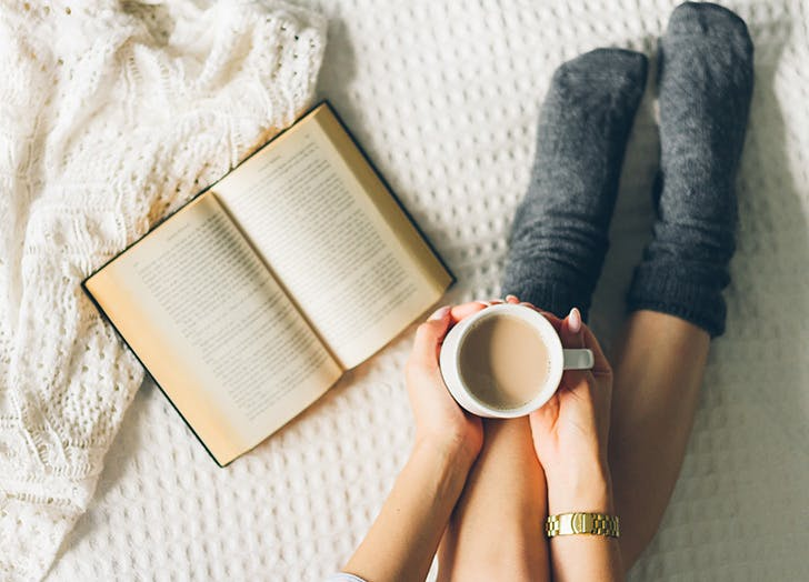 drinking coffee in bed with a book