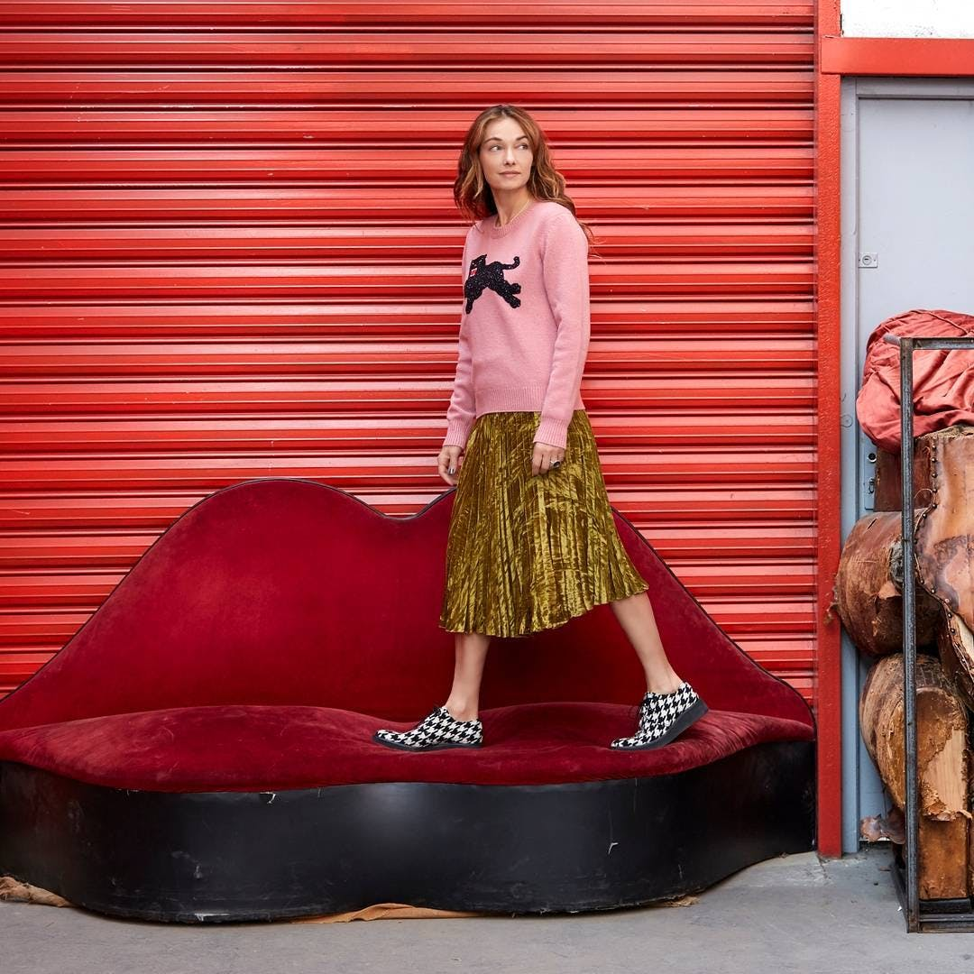 kelly wearstler standing on a vintage couch
