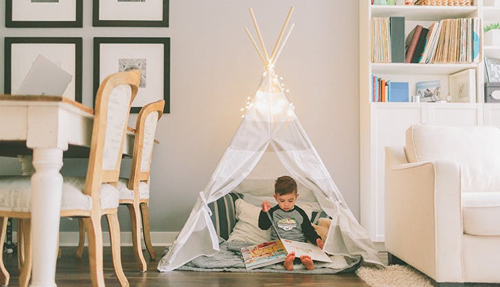little kid reading in his teepee