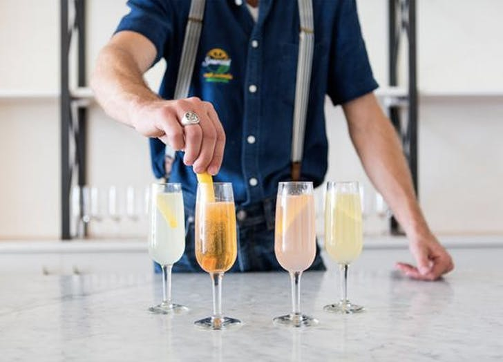 man making french 75 cocktails