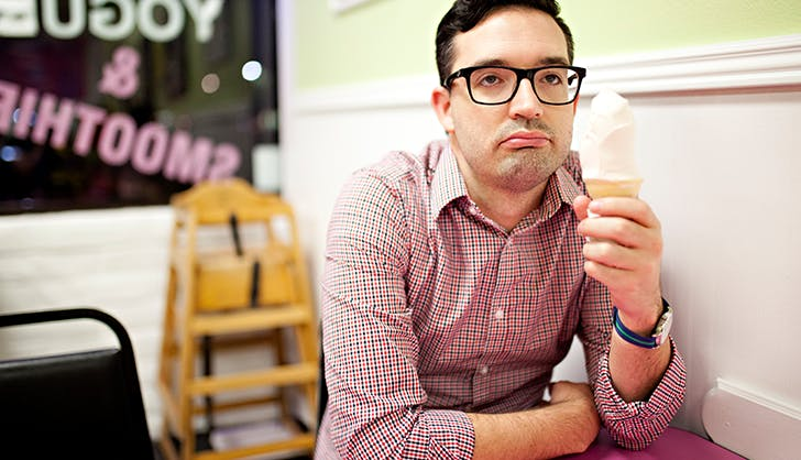 man sadly eating froyo