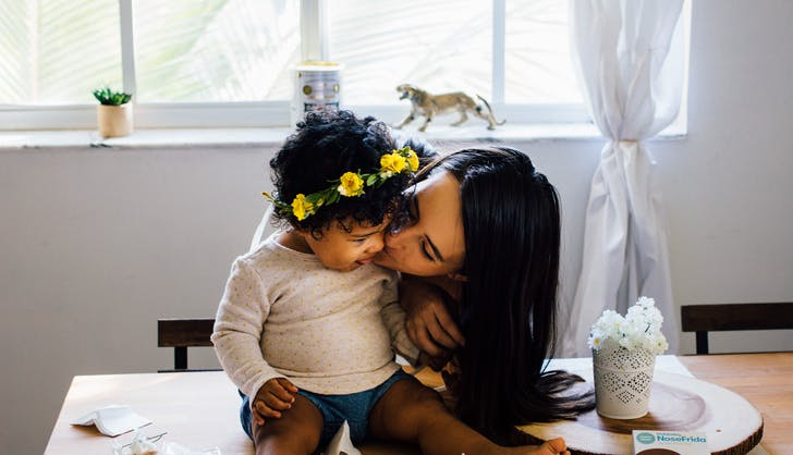 mom kissing her adorable baby daughter on the cheel