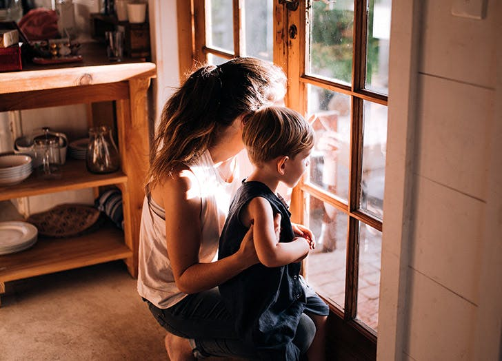 mother and son looking out window