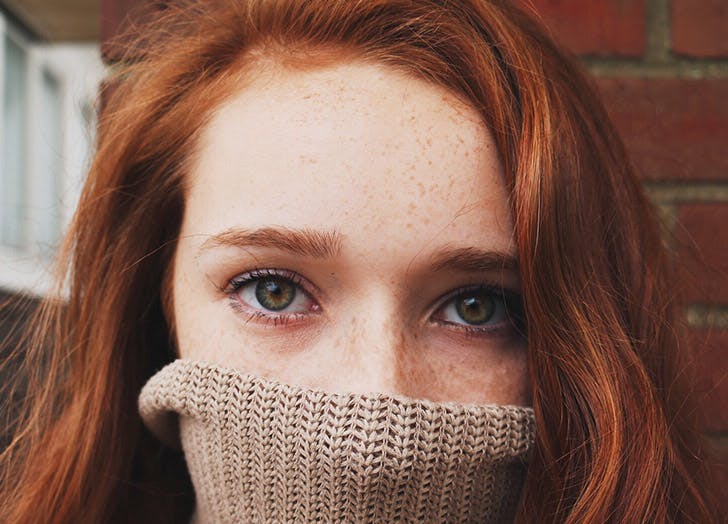 redhead woman with turtleneck over face