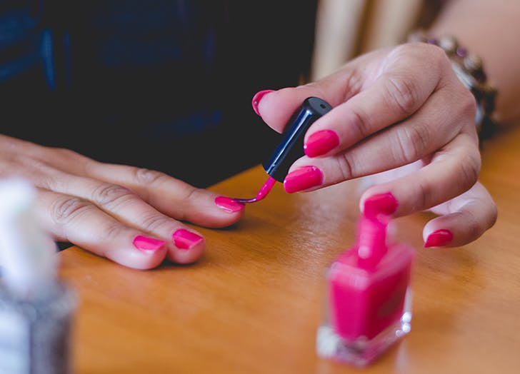 woman painting her nails pink