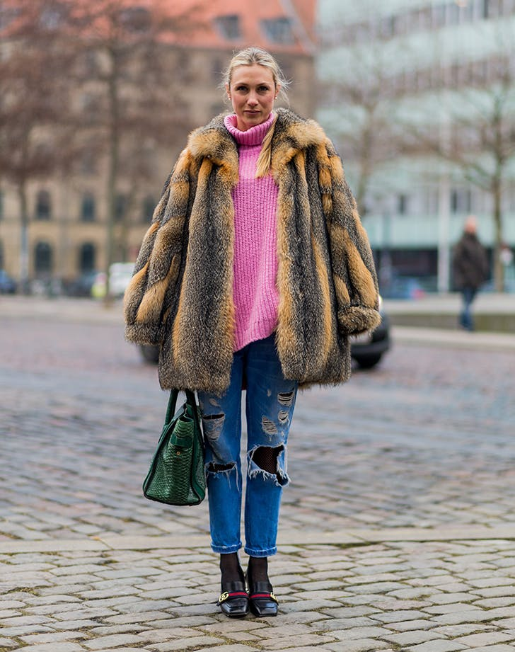 woman wearing a pink sweater fur coat and boyfriend jeans