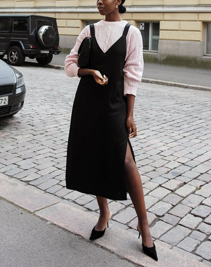 woman wearing a pink sweater under a black dress