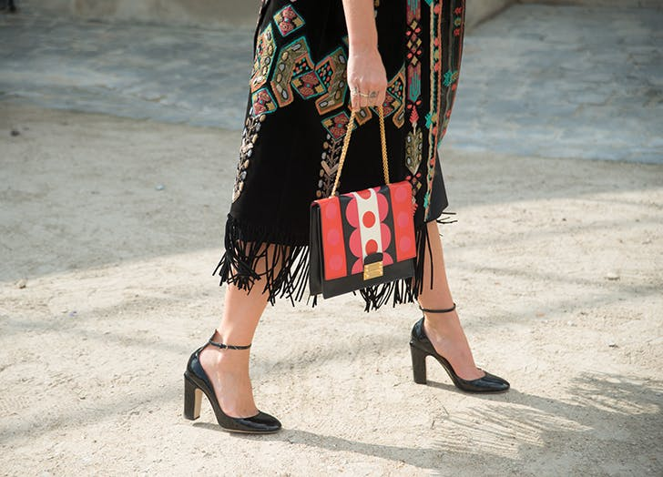 woman wearing a printed skirt and ankle strap heels