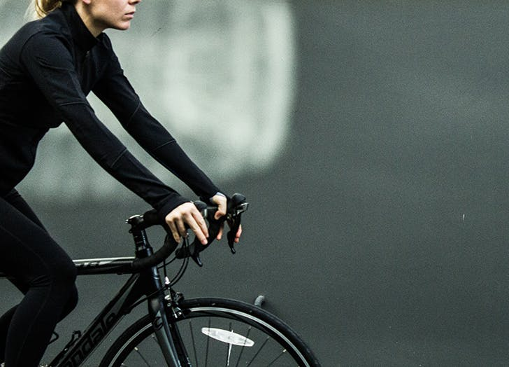 woman wearing all black on a bike