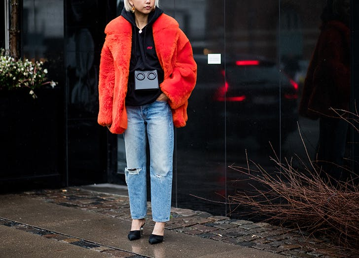 woman wearing black sweatshirt blue jeans and red caot