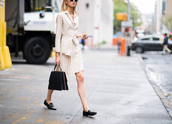 woman wearing cream wrap dress and black loafers