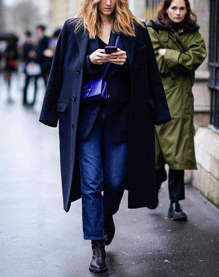 woman wearing dark coat and blue handbag