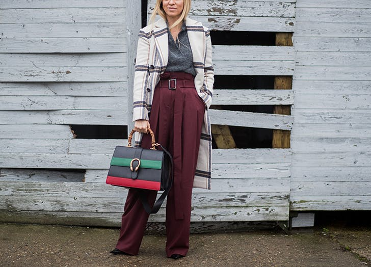 woman wearing high waist pants and a plaid coat
