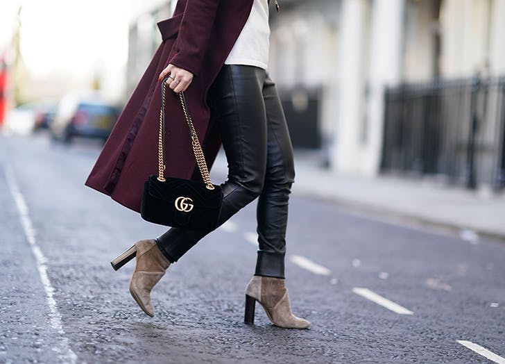woman wearing leather pants and tan ankle boots