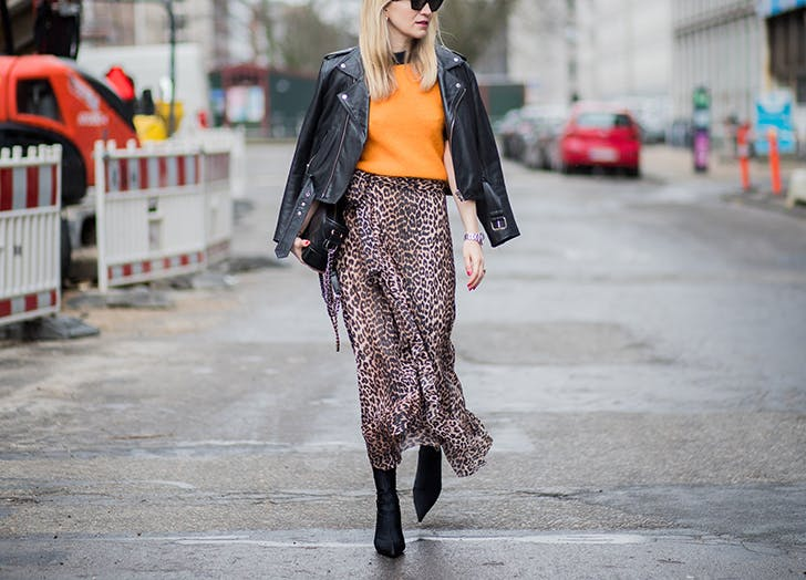 woman wearing leopard skirt orange sweater and black leather jacket