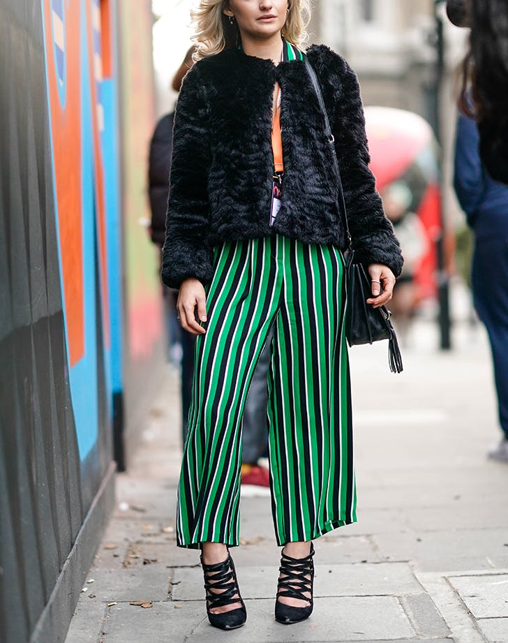 e417ca845c3 woman wearing striped pants and a cropped faux fur jacket
