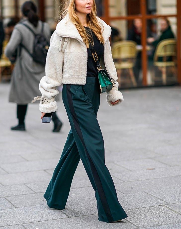woman wearing wide leg pants and a white jacket