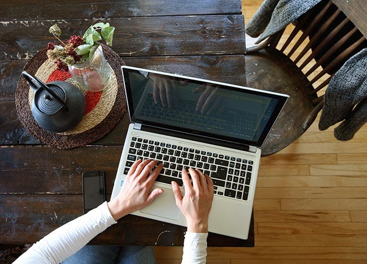 woman typing on laptop at home