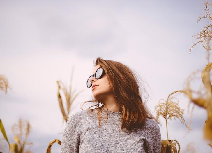 woman wearing sunglasses in a cornfield