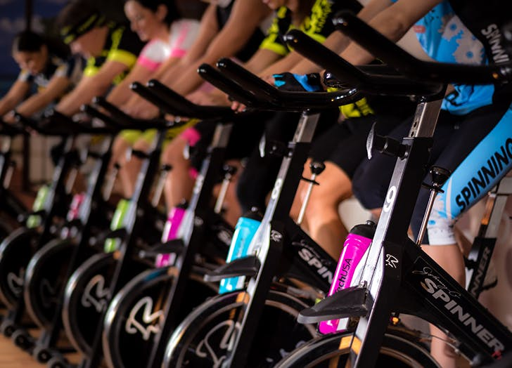 women on bikes in a crowded spin class