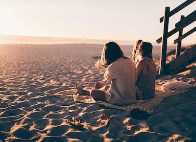 women sitting on beach
