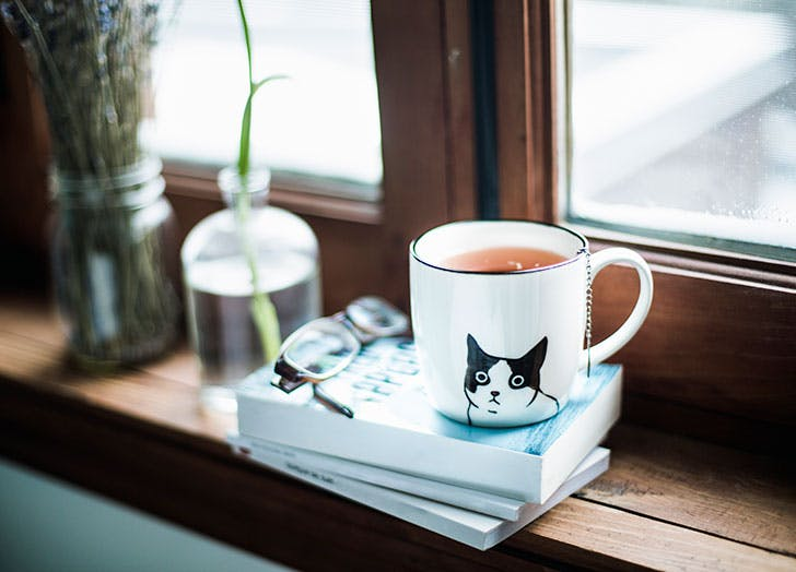 Mug of tea by window sill