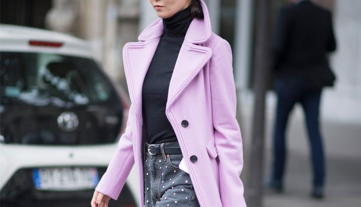 Women wearing lilac coat crosses street