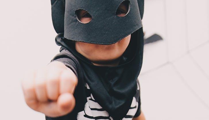 a little kid pretending to be a superhero