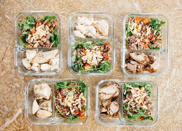 five meal prepped containers of salad and chicken