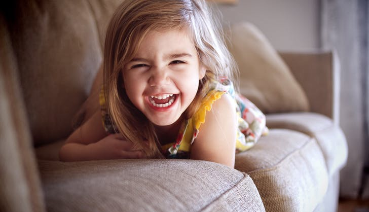 little girl laughing on the couch