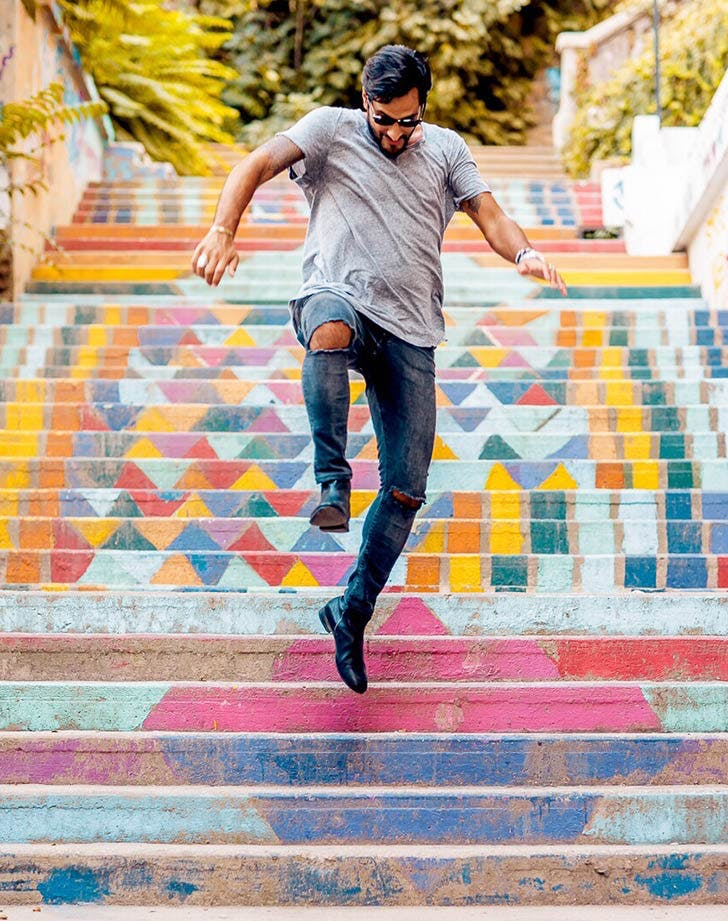 man jumping down colorful staircase
