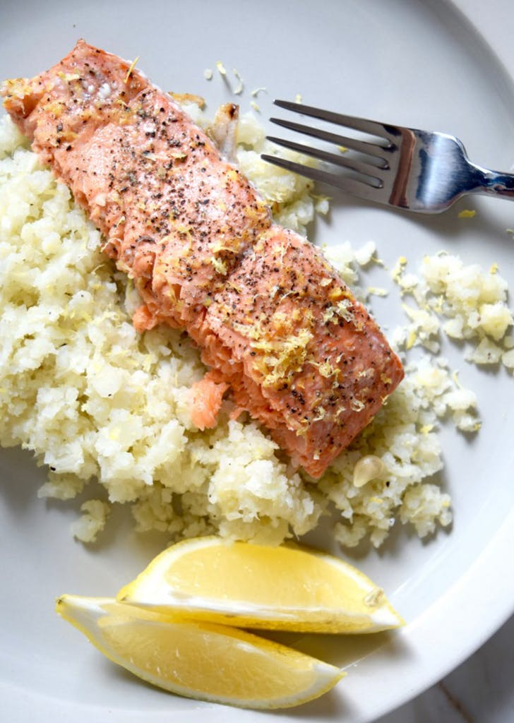 plate with salmon cauliflower rice and lemon