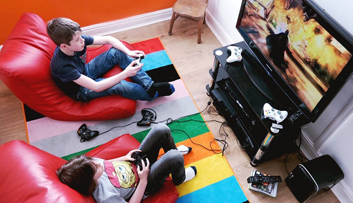 two young boys playing a violent video game