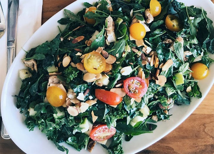 white plate with salad with tomatoes and almonds