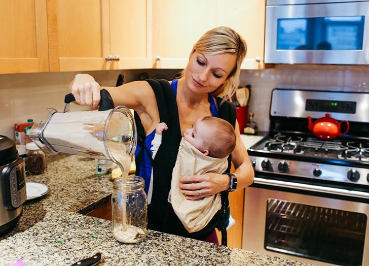 woman holding a baby pouring a smoothie into a glass jar