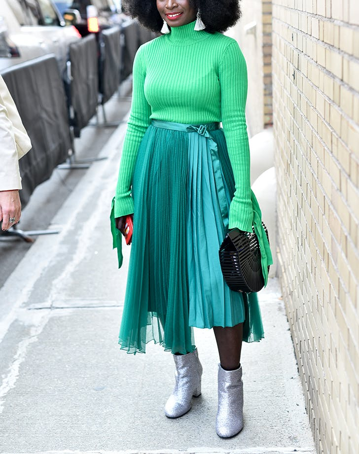 woman wearing a green sweater and pleated midi skirt