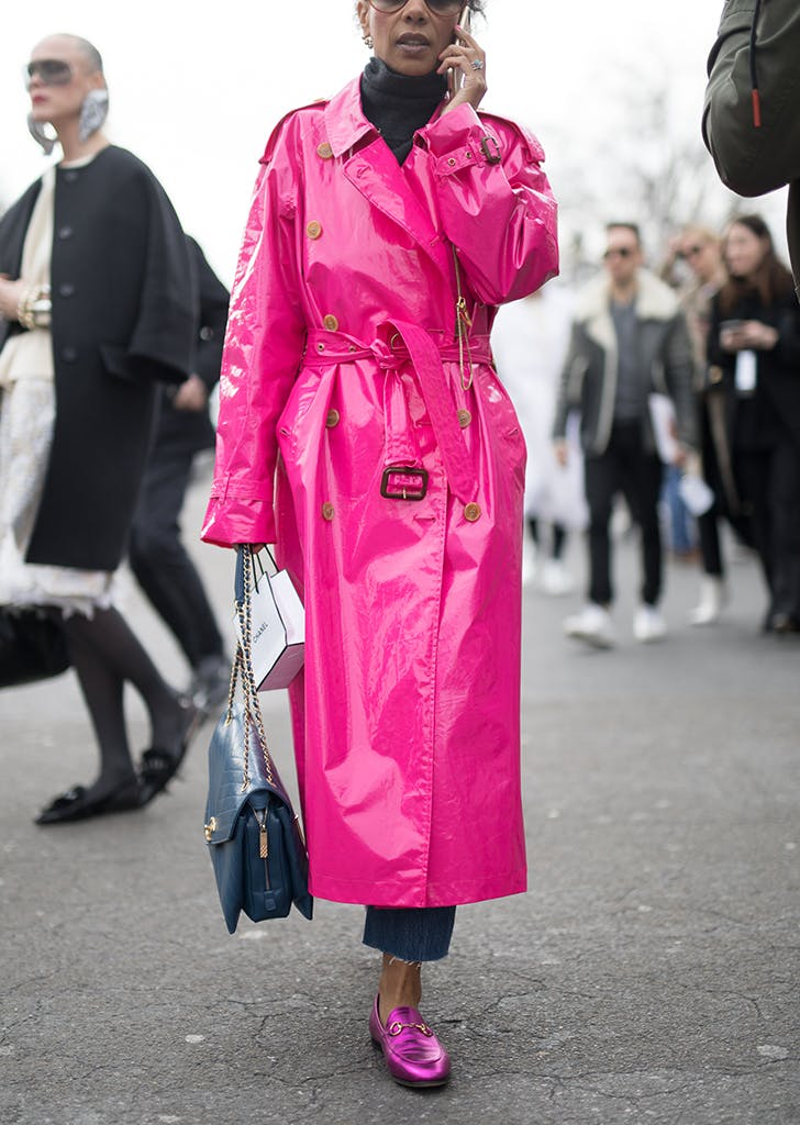 woman wearing a hot pink trench coat and loafers