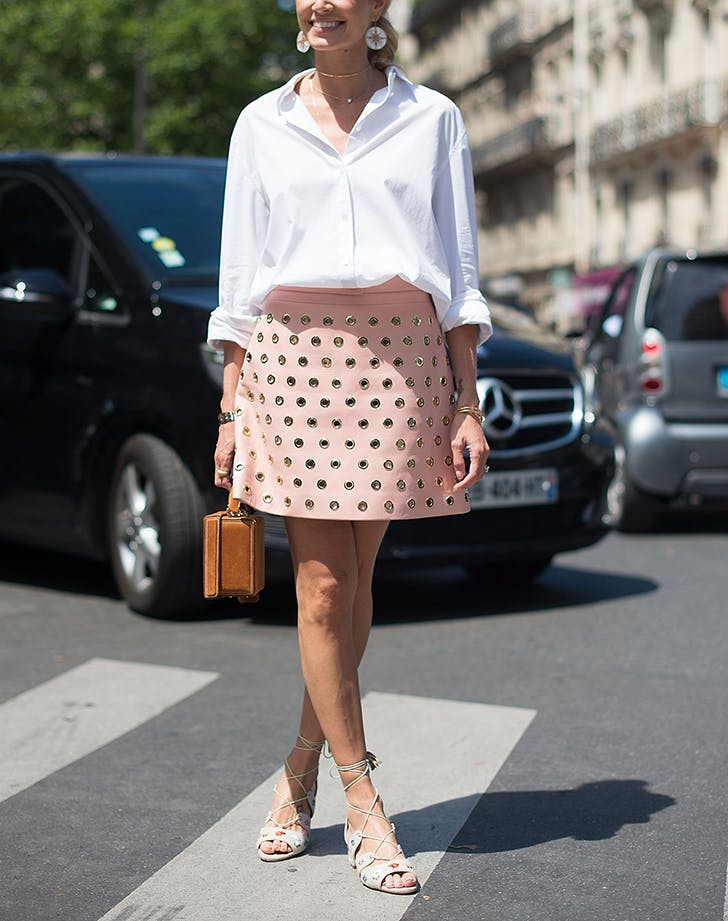 woman wearing a white button down shirt and pink studded miniskirt