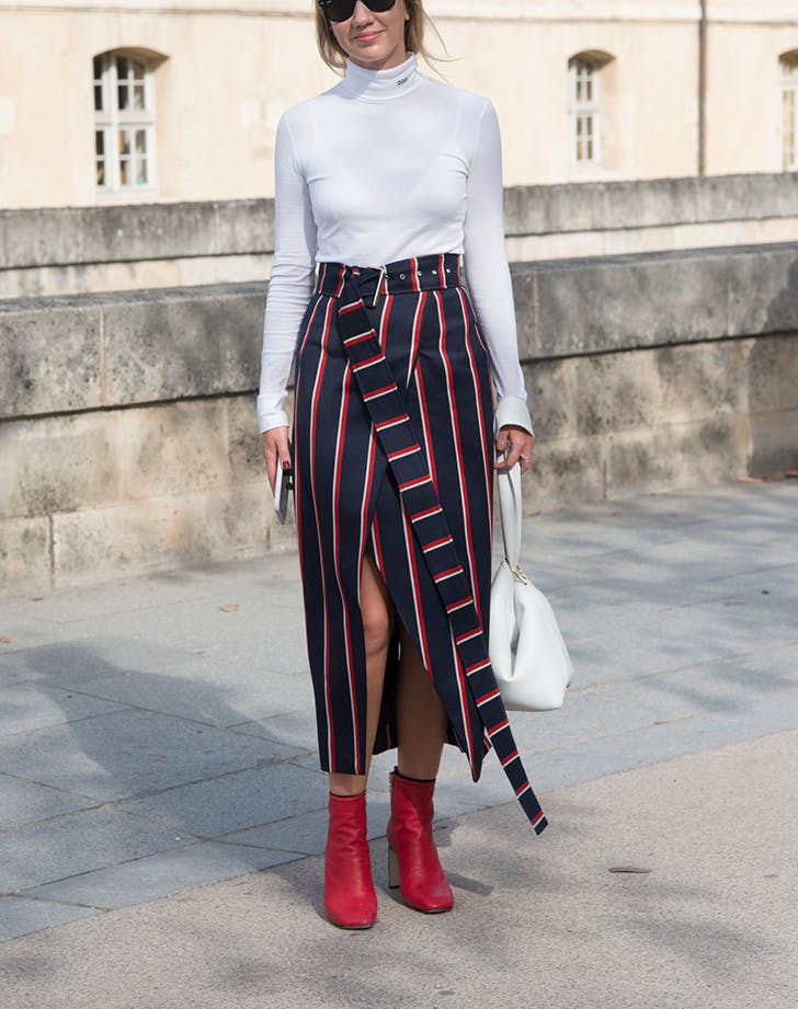 woman wearing a white turtleneck and a striped wrap skirt