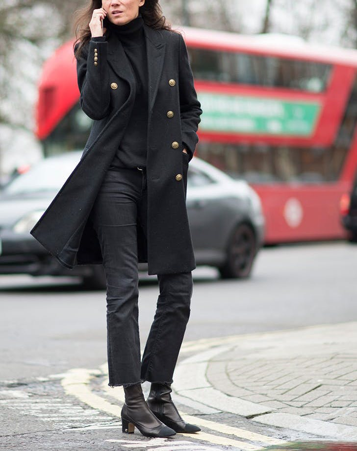 woman wearing black jacket pants and boots