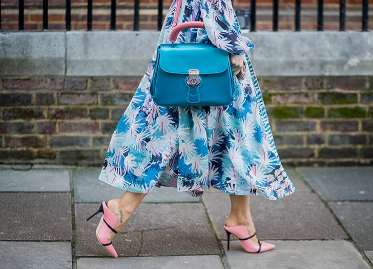woman wearing long blue printed dress and pink heeled mules