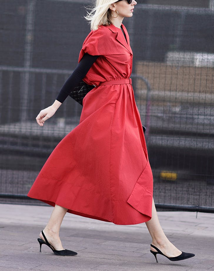 woman wearing red belted coat and slingback pumps
