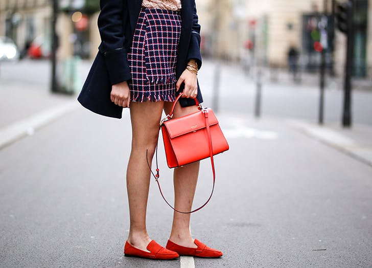 woman wearing short checked skirt flat red loafers and red bag