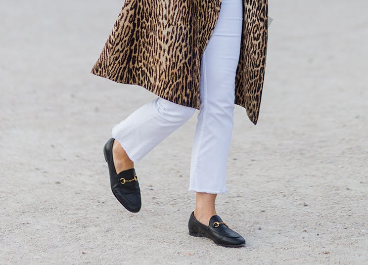 woman wearing white jeans a leopard coat and gucci loafers