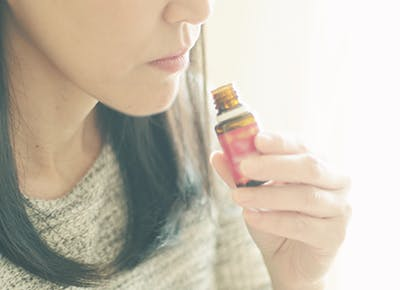 woman smelling essential oil 400