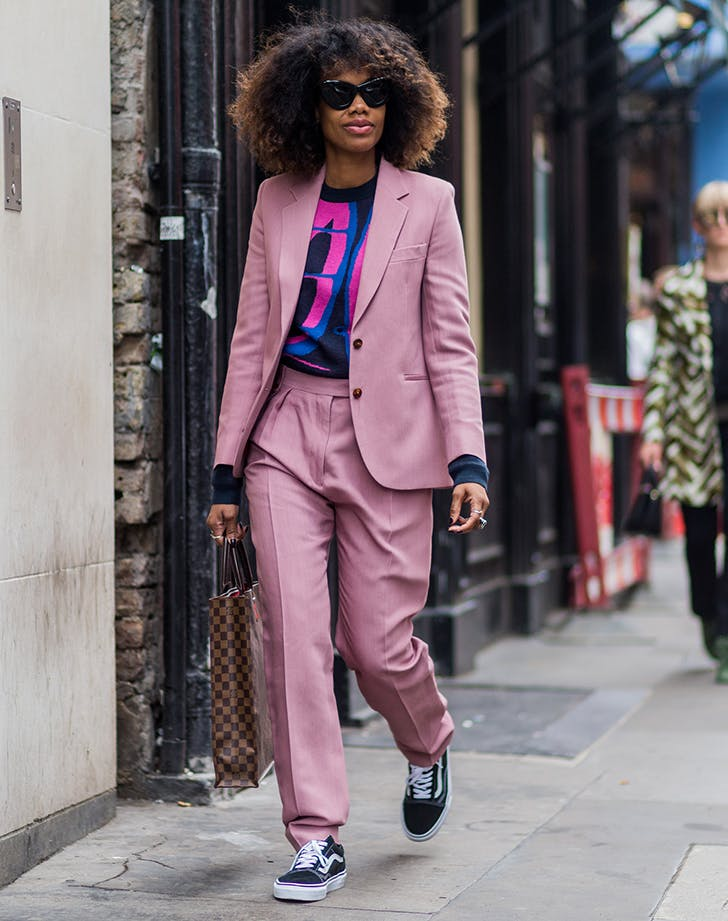 woman wearing a pink suit with a graphic t shirt and sneakers