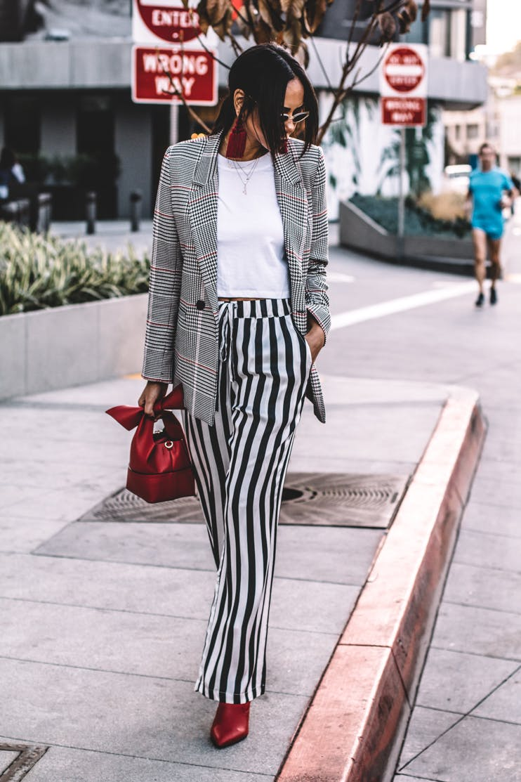 woman wearing a plaid blazer and black and white stripe pants